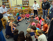 Students and teachers gather in a circle around robots in the Cloverbank Library.