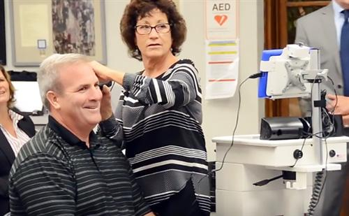 Nurse Suzanne Andelora checks Athletic Director Richard Gray's ear drums with the TeleMedicine cart.
