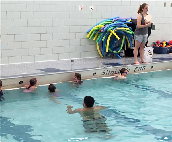 A lifeguard leads children in swim class.