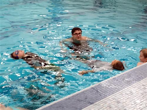 Children float in the pool during swim classes.
