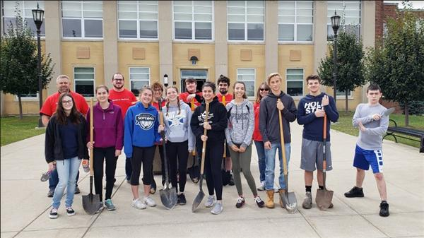 Students volunteered to plant donated trees in front of the high school.